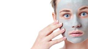 少年skincare概念 有做滑稽的面孔的干黏土面部面具的青少年女孩 库存图片
