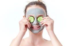 少年skincare概念 有干燥包括她的眼睛的黏土面部面具的青少年女孩用两个切片黄瓜微笑 免版税库存图片