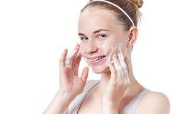 少年skincare 有雀斑和蓝眼睛的微笑的美丽的红头发人青少年的女孩使用起泡沫的清洁剂 库存照片