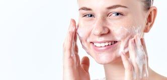少年skincare 有雀斑和蓝眼睛的微笑的美丽的青少年的女孩使用起泡沫的清洁剂 面孔洗涤的概念 免版税库存照片