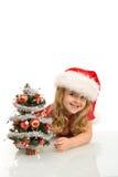 少许偷看微笑的结构树的圣诞节女孩 免版税库存照片