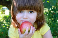 少许吃女孩的苹果 免版税库存图片