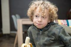 少许吃香蕉的男孩 免版税库存照片
