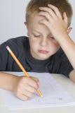 少许执行他的家庭作业的男孩 免版税库存图片