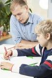 少许执行家庭作业的男孩 免版税库存照片