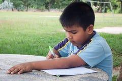 少许执行家庭作业的男孩 免版税图库摄影