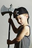 少许野蛮 狂欢节服装的男孩 恼怒的战士 化妆舞会 作为胡子男孩儿童服装礼服穿戴的英国假花梢乐趣愉快的万圣节他的对待窍门佩带的年轻人的海盗嬉戏的准备好的摇摆的剑时间 万圣节 库存图片