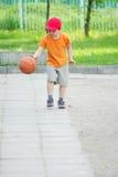 少许滴下篮球的男孩 免版税库存图片