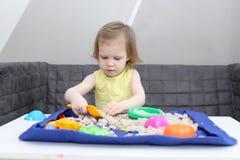 少许2年女孩在家演奏运动沙子 免版税库存照片