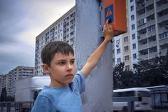 少许7年按在红绿灯的一个按钮和等待绿灯的男小学生 图库摄影
