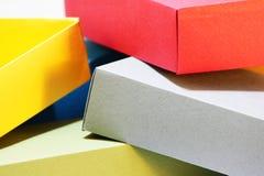 少量五颜六色的纸箱包装的蝶形领结和其他礼物的色的纸板在白色背景 手工制造 免版税库存图片