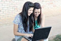 少年不同的女孩的膝上型计算机 免版税图库摄影