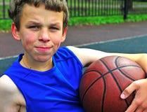 少年与在法院的篮球 免版税库存照片