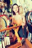少年为羽毛球选择一副新的球拍 免版税库存照片