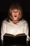 少年书扣人心弦的女孩的读取 库存照片