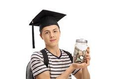 少年佩带的毕业帽子和举行瓶子用mone填装了 免版税库存图片