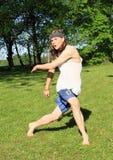 少年使用在草甸的-铁饼选手 免版税库存照片