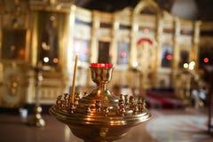 年轻少年光每凝思的教会蜡烛和祈祷 免版税图库摄影