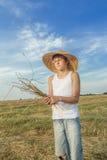 少年农夫拿着捆绑秸杆 库存图片