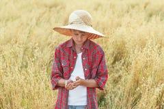 少年农夫男孩画象检查在杯形棕榈的燕麦种子在成熟领域 免版税图库摄影