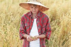 少年农夫男孩画象检查燕麦或燕麦属在杯形棕榈的漂白亚麻纤维的种子 库存照片
