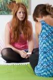 少年告诉她的关于怀孕的朋友 免版税库存图片