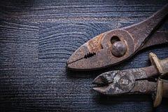 少年和钳子在葡萄酒木头板 免版税库存图片