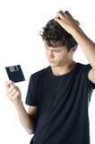 少年困惑与软盘在他的手上 库存图片