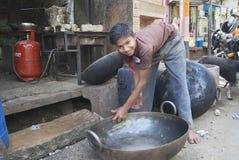少年在乔德普尔城,印度洗涤金属木盆 免版税库存图片