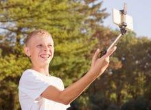 少年在公园做selfie 免版税库存照片