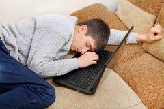 少年在膝上型计算机睡觉 库存照片