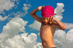 少年在绯红色在天空和云彩背景的班丹纳花绸热的晴天  免版税库存照片