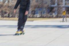 少年在pennyboards乘坐在一个晴朗的春日 背景迷离弄脏了抓住飞碟跳的行动 免版税库存照片