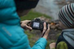 少年坐在营火附近的在露营地和神色入照相机 免版税库存照片