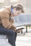 少年坐长凳和祈祷 库存照片