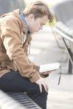 少年坐长凳读书圣经 库存图片