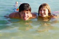 少年夫妇在水中 库存照片