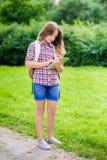 少年女孩与背包在她的手上的拿着数字式片剂 免版税库存图片