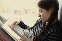 少年女孩与茶杯的阅读书 免版税库存照片