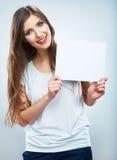 少年女孩举行白色白纸。年轻微笑的妇女展示 库存图片