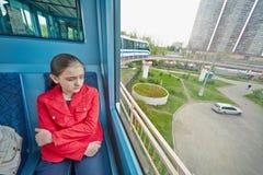 少年女孩在莫斯科单轨铁路车系统支架乘坐  免版税库存照片