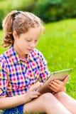 少年女孩坐与数字式片剂的草 免版税库存图片