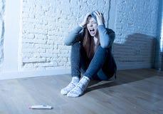 年轻少年女孩或少妇震动的在正面妊娠试验以后惊吓了 免版税库存图片