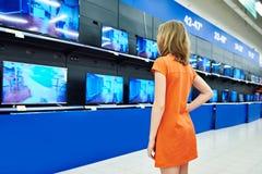 少年女孩看LCD电视在商店 库存照片