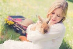 少年女孩葡萄酒照片有兔宝宝的在自然 免版税库存照片