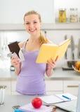 少年女孩阅读书和吃巧克力 免版税库存照片