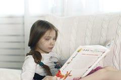 少年女孩读一本书,当时 免版税图库摄影