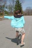 年轻少年妇女下来骑马单轮脚踏车住宅街道 免版税图库摄影
