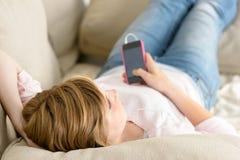 少年妇女在沙发放松听音乐 免版税库存图片