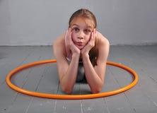 少年嬉戏女孩做着与hula箍的锻炼发展在灰色背景的肌肉 获得打比赛的乐趣 体育愈合 免版税库存照片